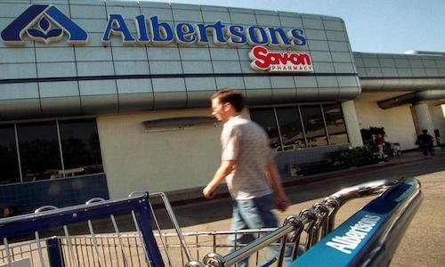 A man walking toward an Albertsons market.